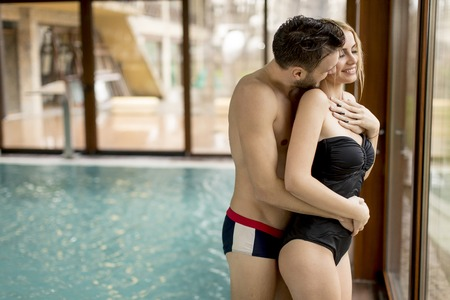 Loving couple relaxing in the spa center by pool