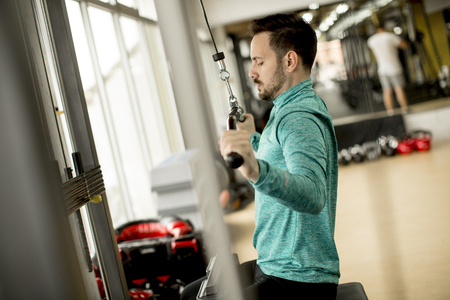 Handsome man doing excersise on a lat machine in gym