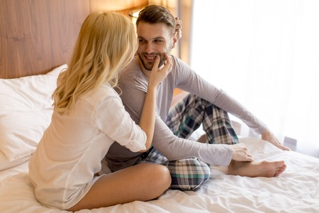 Young adult heterosexual couple on bed in bedroom at home Stock Photo