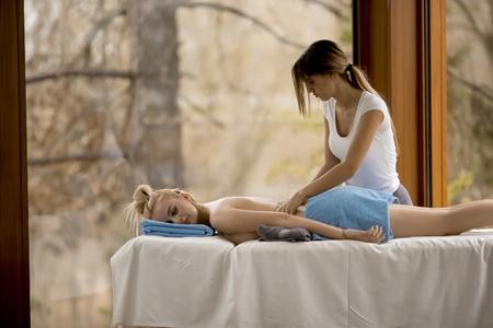Beautiful blond woman enjoying a massage at the health spa Imagens
