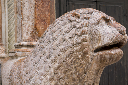 View at sculpture of lion with pray in front of Duomo in Modena, Italy