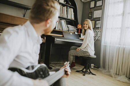 Young piano player accompanied by a handsome male guitarist Foto de archivo - 131582100