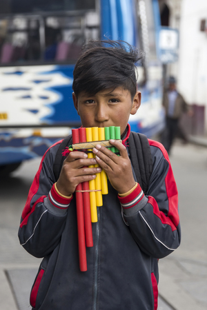 LA PAZ, BOLIVIA - JANUARY 12, 2018: Unidentified boy with pan flute at street of La Paz, Bolivia. At an elevation of 3650 m La Paz is the highest capital city in the world