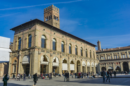 BOLOGNA, ITALY - FEBRUARY 15, 2018: Unidentified people by the Podesta Palace in Bologna, Italy. This civic building at Piazza Maggiore was built around 1200. Sajtókép