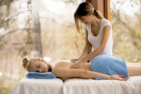 Beautiful blond woman enjoying a massage at the health spa 版權商用圖片