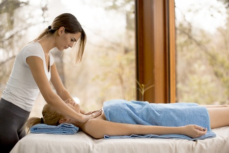 Pretty young blonde woman having a massage in the wellness center 写真素材