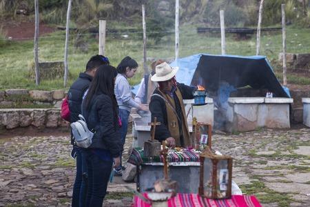 コパカバーナ、ボリビア - 1月 7, 2018: ボリビアのコパカバーナの路上で煙の儀式を行う不一人の男性.コパカバーナはチチカカ湖の主要なボリビアの