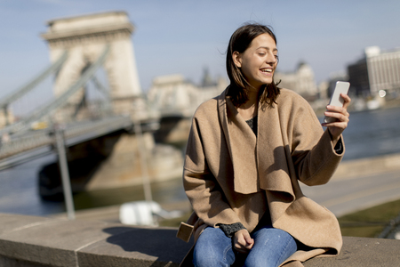 Young woman using mobile phone with Chain bridge at background in Budapest, Hungary