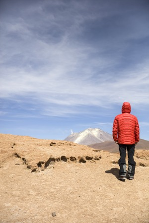 Young man looking at View at Licancabur volcano in Reserva Nacional de Fauna Andina Eduardo Avaroa in Bolivia Imagens