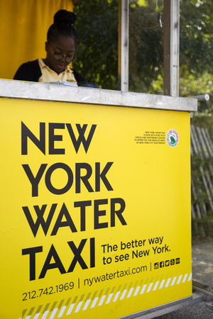 NEW YORK, USA - AUGUST 27, 2017: Unidentified woman working at New York water taxi desk. Water taxi service was founded at 20012 and now have  13 llines with 12 vessels mainly on East and Hudson River