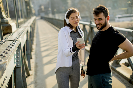 Young athletic couple is having a rest after jogging in the city