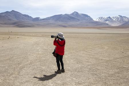 Young woman taking photo at Dali desert at Eduardo Avaroa Andean Fauna National Reserve in Bolivia Imagens