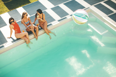 Young women drinking coctail and having fun by swimming pool at hot summer day Stock Photo