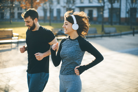 Healthy couple running in  city cityscape background