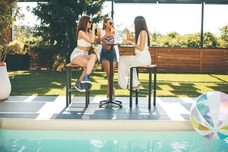 Pretty young women drinking coctail and having fun by the pool at hot summer day