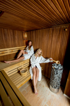 Two pretty young women in wellness spa center relaxing in wooden sauna