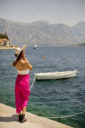 Pretty young attractive woman with a hat poses by the sea in the summer
