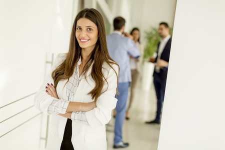 Young businesswoman standing in the office and other young business  people talking in the background