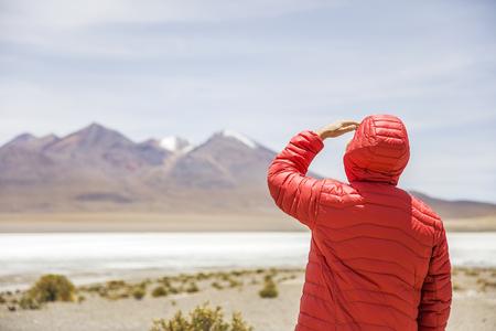 ボリビアのエドゥアルド・アヴァロア・アンデアン動物保護区のラグーンと山々を見る若者