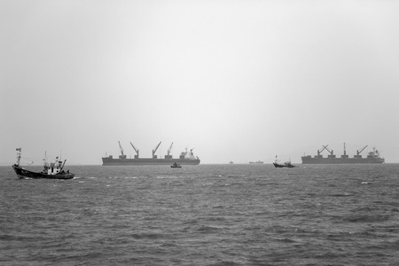 Industrial ships in the waters of Mumbai, India. The port and shipping industry employs many residents directly and indirectly. Stock Photo - 98984135