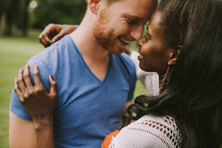 Happy young lovely multiracial couple in the park on a summer day