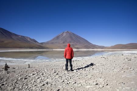 Young man looking at Laguna Verde lake and Licancabur volcano in Reserva Nacional de Fauna Andina Eduardo Avaroa in Bolivia