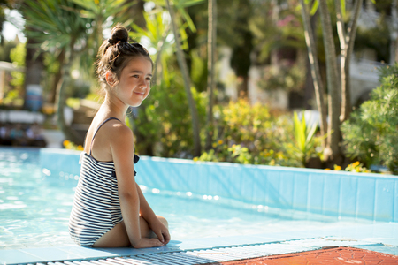 Cute little girl on the poolside on a sunny summer day