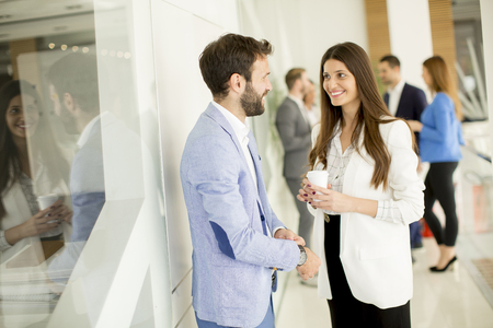 Young business partners talking in modern office