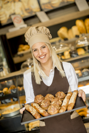 Beautiful female bakery posing with various types of pastries and breads in the bakery