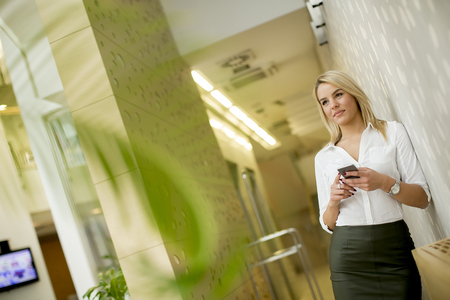 Young businesswoman with mobile phone standing in the modern office Foto de archivo