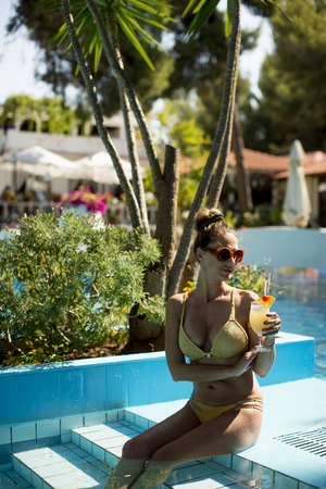 Pretty young woman by the swimming pool with cocktail