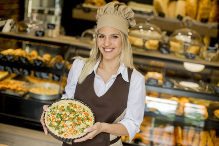 Pretty young woman with quiche lorraine in the bakery
