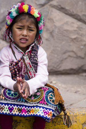 CUSCO, PERU - DECEMBER 31, 2017: Unidentified girl on the street of Cusco, Peru. Almost 29% of Cusco population have less than 14 years. 新聞圖片