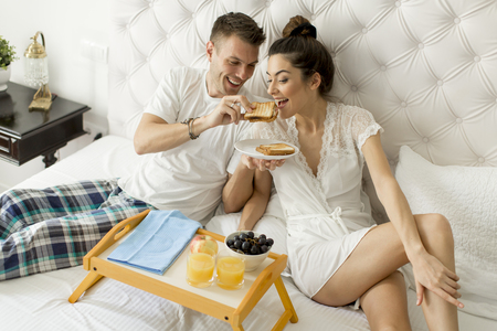 Young loving couple having breakfast in bed
