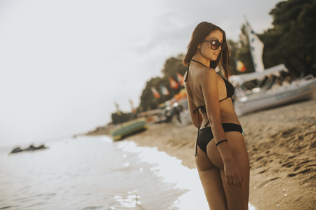 Fit and sporty woman in a swimsuit relaxing on a beach at summer