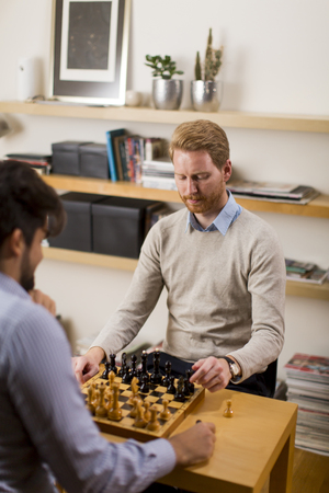 Two young men playing chess in room