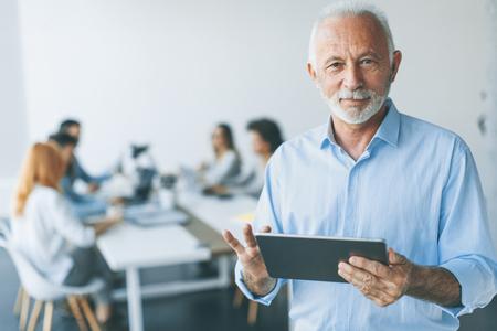 Retrato del empresario senior de pie con tableta digital en la mano