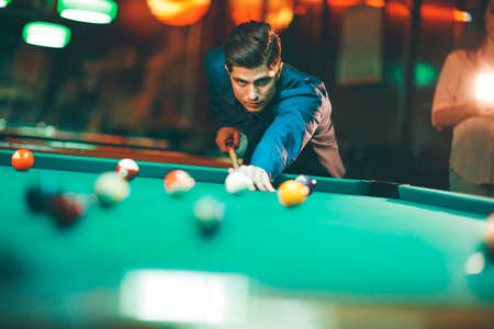 Young man playing pool in the bar Фото со стока