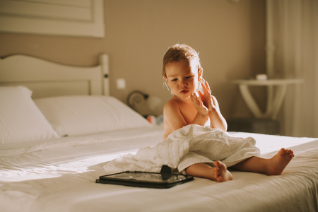 Sweet curly little girl with a towel over her wet body siting in a bedroom after shower or bath Stock Photo