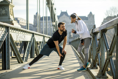 Young handsome couple have training in urban enviroment at sunny day Stock Photo