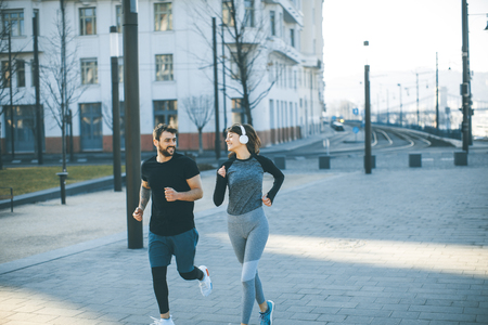 Healthy young couple running in the city with cityscape in background