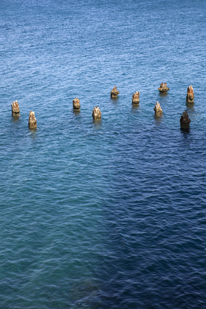 Remains of the old wooden pillars in the sea Imagens