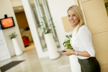 Portrait of a beautiful young businesswoman standing in the modern office using mobile phone Stock Photo