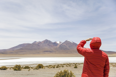 Young man lookinag at lagoon and mountains at Eduardo Avaroa Andean Fauna National Reserve in Bolivia 写真素材