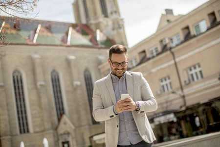 Portrait of a young businessman holding digital tablet outdoor in urban enviroment