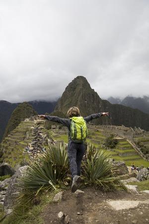 Young woman standing above Machu Picchu Inca citadel in Peru
