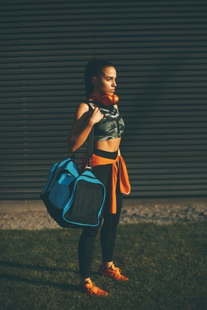 Young woman standing with sport bag outdoor after training