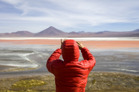 Young man taking photo at Laguna Colorada at Eduardo Avaroa Andean Fauna National Reserve in Bolivia