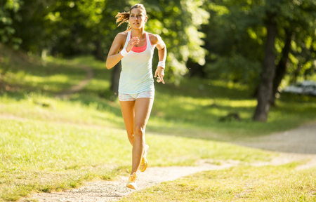 View at young woman running in park on beautiful summer day