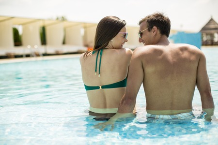 Young couple relaxing by the swimming pool on a sunny day Banque d'images